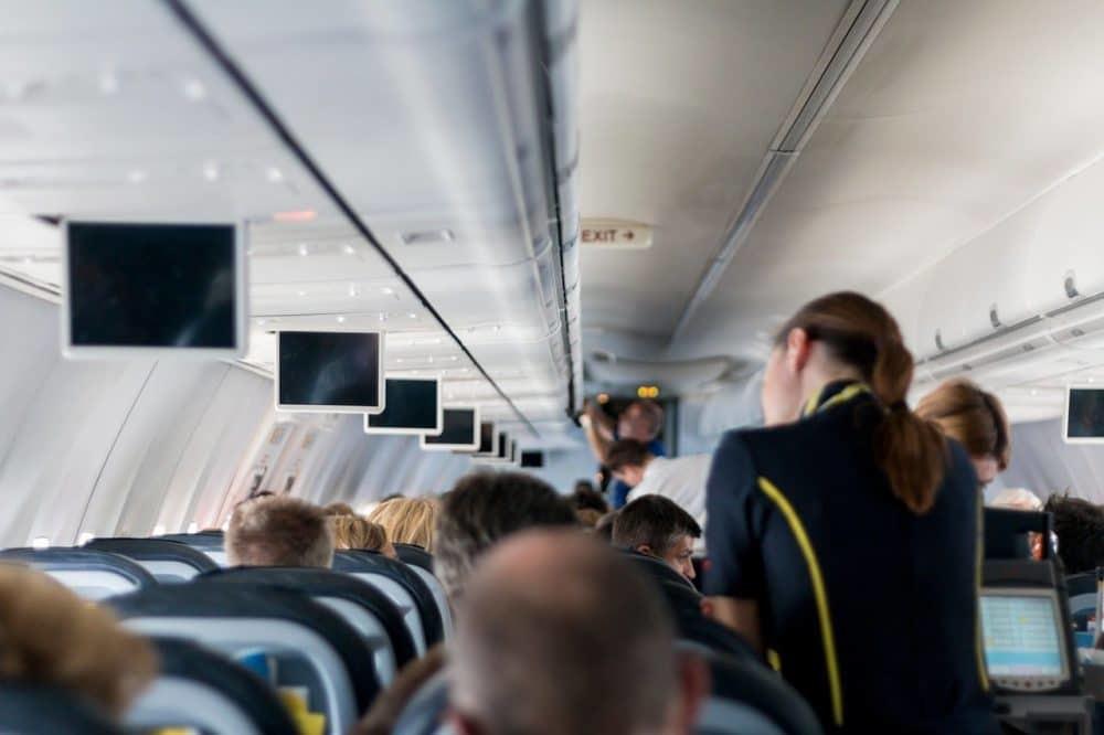 Bordkabine eines Flugzeuges mit Passagieren und Stewardess