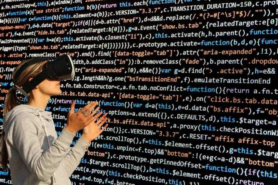Frau mit VR-Brille, HTML-Code im Hintergrund